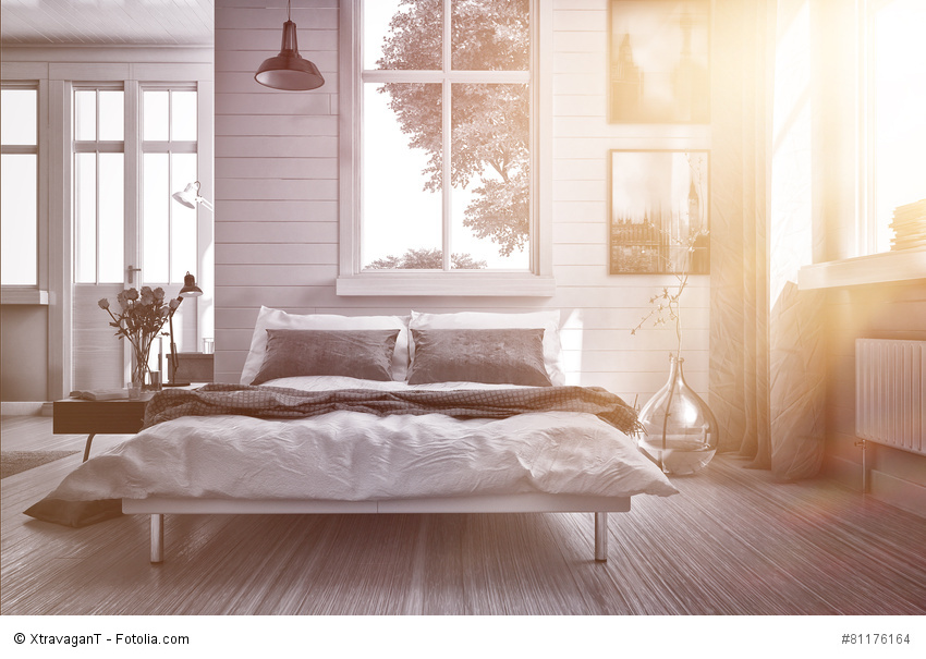 Luxury spacious airy bedroom lit by warm glowing sun flare streaming in through one of the multiple windows with modern grey and white decor and a double divan bed